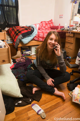 girl is sitting barefoot on the floor of her messy bedroom talking